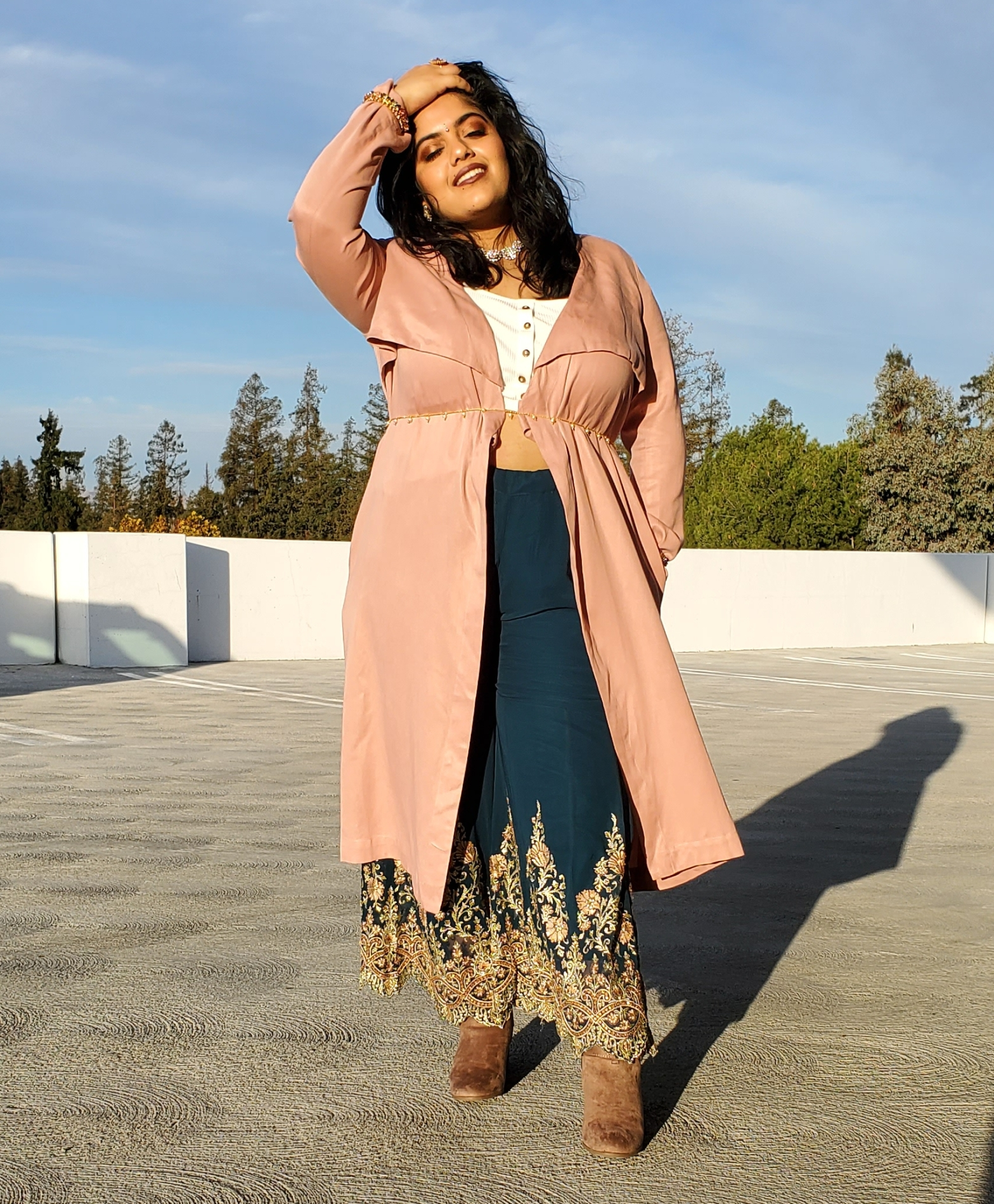 Renuka standing in an indowestern outfit with teal embroidered pants and a pink trench coat